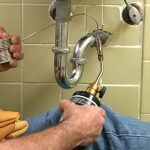 A plumber using a welding torch to solder pipe in the bathroom.